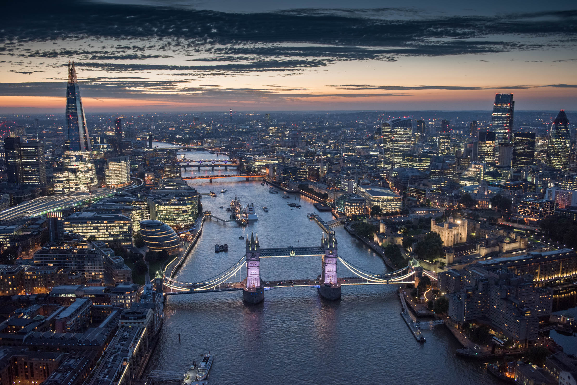 a view of Tower Bridge, Just after dusk, More London and the City of London, the Shard, with dispensation from the CAA down to 600ft. Date : September 2016